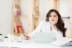 Tired beautiful Businesswoman holding hand on head while working on computer and some business documents in bright. Office royalty free stock images