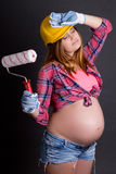 Tired beautiful pregnant woman in builder's helmet with  paint b Stock Photography