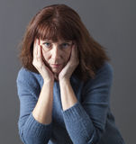 Tired beautiful 50s woman looking upset. Portrait of mature woman with brown hair and blue winter sweater thinking,face leaning on both hands,staring with Royalty Free Stock Photos