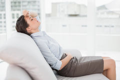 Tired beautiful well dressed woman sitting on sofa at home Stock Photography