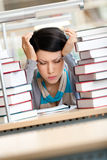 Tired beautiful woman surrounded with books. Tired beautiful woman with headache sitting at the desk surrounded with piles of books Royalty Free Stock Photos