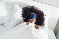 Tired Black Girl Waking Up In Bed With Sleep Mask Royalty Free Stock Photography