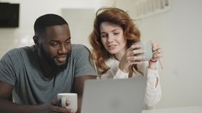 Tired black man looking laptop screen at home. Woman bringing tea to guy.
