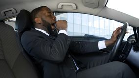 Tired black man yawning in car, overworked businessman driving car, danger. Stock photo stock images