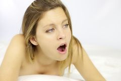 Tired blond beauty yawning in bed Royalty Free Stock Photography