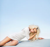 Tired blond lady lying on the ground stock photography