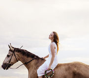 Tired blond woman resting by riding a horse Royalty Free Stock Images