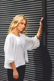 Tired blonde business woman touching black wall outdoors. Tired blonde business woman in elegant summer clothing touching black wall outdoors. Split toned photo royalty free stock images