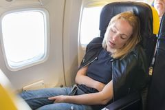 Tired blonde casual caucasian lady napping on seat while traveling by airplane. Tired blonde casual caucasian lady napping on exit window seat while traveling Stock Photos