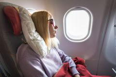 Tired blonde casual caucasian lady sleepin on seat while traveling by airplane. Commercial transportation by planes. royalty free stock photos