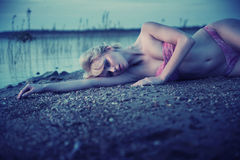 Tired blonde girl lying on the beach Stock Images