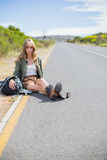 Tired blonde woman sitting on the roadside Royalty Free Stock Images