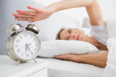 Tired blonde woman turning off her alarm in the morning Stock Photos