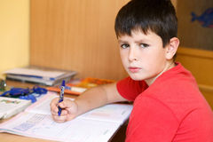 Tired and bored boy doing school homework Stock Photography