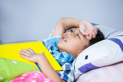 Tired and bored boy unhappy. Studying hard, education concept. Tired and bored kid unhappy when he read a book on bed in bedroom. Children read and study Stock Photo