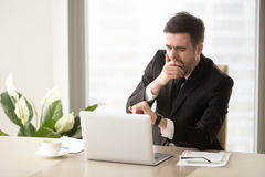 Tired bored businessman yawning at workplace, checking time on w. Tired bored businessman yawning at workplace near laptop, looking at wristwatch, checking time Royalty Free Stock Images
