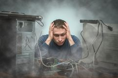 Computer repairman. Computer technician engineer. Support service. Tired and bored computer repairman is sitting on his workplace in smoke of burning hardware Stock Image