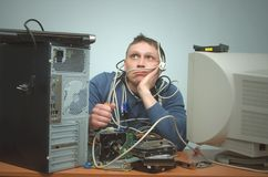 Computer repairman. Computer technician engineer. Support service. Tired and bored computer repairman is sitting on his workplace and thinking. Computer Royalty Free Stock Images