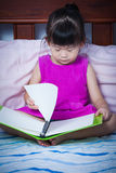 Tired and bored girl sleeping when she read a book. Education co. A little cute asian girl in a purple dress sleeping when she read a book on bed in bedroom Royalty Free Stock Photo