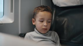 Tired and bored kid traveling by train. Cinemagraph - Tired boy traveling by train. He sitting in leather seat, passing scenes in the window stock video footage