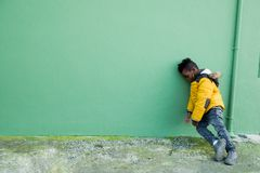 Tired and bored little boy on the street. Tired and angry little boy in yellow coat leaning on a green wall on the street Stock Photo