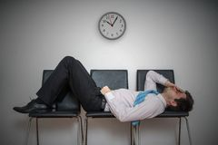 Tired bored man is sleeping in waiting room on chairs. royalty free stock photo