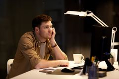 Tired or bored man on table at night office. Business, overwork, deadline and people concept - tired or bored man on table at night office Royalty Free Stock Image