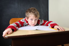 Tired and bored student. A student sprawls across his desk looking tired and bored Stock Images