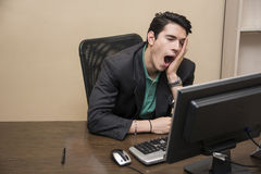 Tired bored young businessman sitting in office Royalty Free Stock Photo
