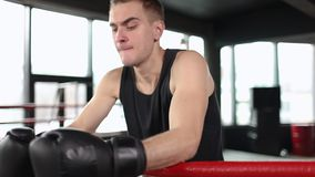 Pause in Boxing Workout. Tired boxer man dressed in black t-shirt and gloves have rest near arena ropes stock footage