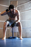 Tired boxer wiping the sweat while sitting on ring Royalty Free Stock Photos
