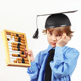Tired boy in academic hat with old abacus on white background Royalty Free Stock Photo