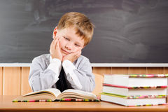 Tired  boy with books at the desk Stock Images
