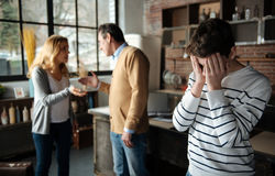 Tired boy bowing his head while covering face. Want happy family. Angry parents standing on the background while gesticulating and sorting out theirs Royalty Free Stock Image
