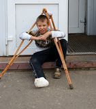 Tired boy with broken leg and wooden crutches outdoor. Tired boy with broken leg and wooden crutches sitting on the door sill outdoor Royalty Free Stock Images