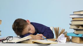 Tired boy fell asleep at a desk between books. Blue background stock video