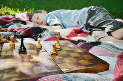 tired boy fell asleep after a game of chess. focus on chess figures stock images