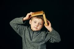 Tired boy holding a book over his head. The concept of pre-school education Royalty Free Stock Photos