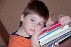 Tired boy with a pile of books Stock Photo