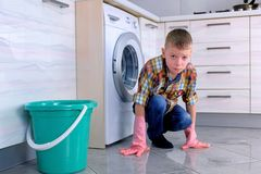 Tired boy in rubber gloves don`t want to wash the floor in the kitchen. Child`s home duties. Tired boy in rubber gloves don`t want to wash the floor in the stock photo