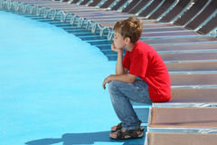 Tired boy sits on edge of deck-chair. On blue deck of cruise liner royalty free stock photography