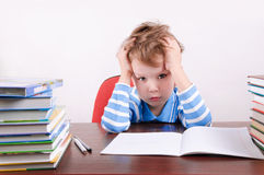 Tired boy sitting at a desk and holding hands to head. Tired little boy sitting at a desk and holding hands to head. boy 5 years. on the desk a lot of books Royalty Free Stock Photos