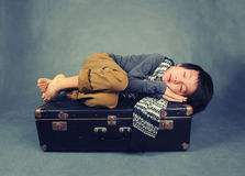 A tired boy sleeping on suitcase stock photo
