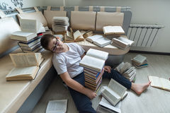 Tired boy sleeping surrounded by books in  room Stock Photos