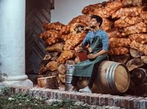 Tired brewer in apron sitting on a barrel and drinks craft beer relaxing after work. Tired brewer in apron sitting on a barrel and drinks craft beer relaxing stock photos