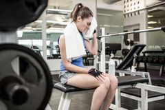 Tired brunette on bench wiping sweat with towel Royalty Free Stock Photo