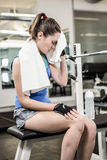 Tired brunette on bench wiping sweat with towel Royalty Free Stock Photos