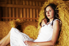A tired brunette girl is relaxing on a pile of hay Royalty Free Stock Photo