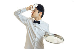 Tired brunette waiter man in unifrom with silver tray in hand Royalty Free Stock Photo