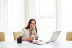Tired brunette working in the modern spacious office Royalty Free Stock Photo